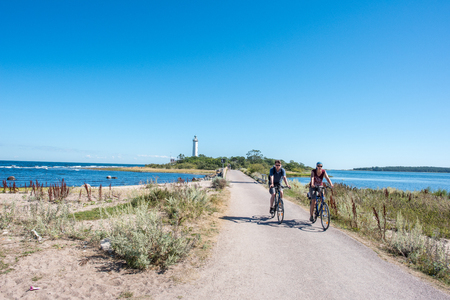 oland: Oland, Sweden  August 16, 2015: Tourists on bikes after visiting famous lighthouse Lange Erik  Tall Erik on the northern point of Swedish Baltic Sea island Oland.
