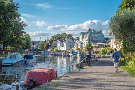 tourist destination: Trosa, Sweden  August 6, 2015: Leisure boats moored at the harbor along the outflow of Trosa river into the Baltic sea. Trosa is an idyllic and historic seaside town south of Stockholm and a popular tourist destination during summer time. Editorial