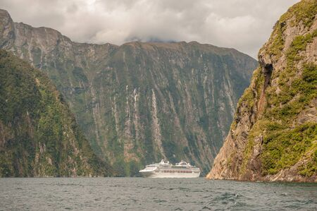 fiord: Milford Sound, New Zealand  February 14, 2012: Cruise ship cruising in Milford Sound. This fiord is considered as one of the most scenic places in the world.