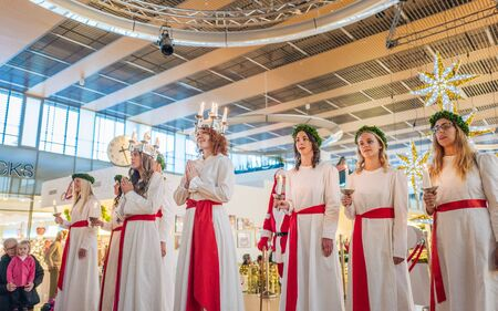 christmas carols: Norrkoping, Sweden - December 13, 2015: Lucia celebration in a mall in Norrkoping. The celebration of Lucia or Saint Lucy is one of the dearest traditions in Sweden before Christmas.