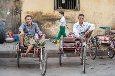 ethnically diverse: Yangon, Myanmar - February 10, 2014: Burmese rickshaw drivers  taking a break in Chinatown. Myanmar is ethnically diverse with 51 million inhabitants belonging to 135 ethnic groups. Editorial