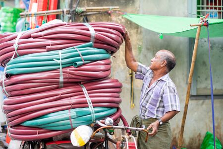 ethnically diverse: Yangon, Myanmar - February 10, 2014: Burmese man prepares a transport of tubing on a bicycle. Myanmar is ethnically diverse with 51 million inhabitants belonging to 135 ethnic groups.