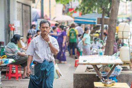 51: Yangon, Myanmar - February 10, 2014: Burmese man wearing traditional longyi walks along Maha Bandoola Road in Chinatown. Myanmar is ethnically diverse with 51 million inhabitants belonging to 135 ethnic groups. Editorial