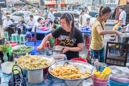 Yangon, Myanmar - February 5, 2014: Burmese people selling street food at the street market on Maha Bandoola Road in Chinatown. Myanmar is ethnically diverse with 51 million inhabitants belonging to 135 ethnic groups.