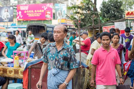 ethnically diverse: Yangon, Myanmar - February 10, 2014: Burmese man wearing traditional longyi walks along Maha Bandoola Road in Chinatown. Myanmar is ethnically diverse with 51 million inhabitants belonging to 135 ethnic groups. Editorial