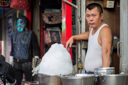 inhabitants: Yangon, Myanmar - February 10, 2014: Burmese market vendor in Chinatown. Myanmar is ethnically diverse with 51 million inhabitants belonging to 135 ethnic groups. Editorial