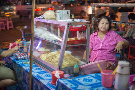 night market: Yangon, Myanmar - February 10, 2014: Burmese woman selling street food at the night market on Maha Bandoola Road in Chinatown. Myanmar is ethnically diverse with 51 million inhabitants belonging to 135 ethnic groups. Editorial