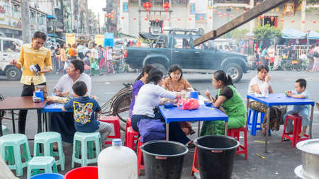 ethnically diverse: Yangon, Myanmar - February 5, 2014: Burmese people eating street food at the street market on Maha Bandoola Road in Chinatown. Myanmar is ethnically diverse with 51 million inhabitants belonging to 135 ethnic groups.
