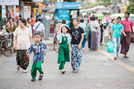 ethnically diverse: Yangon, Myanmar - February 5, 2014: Burmese people crossing a street along Maha Bandoola Road in Chinatown. Myanmar is ethnically diverse with 51 million inhabitants belonging to 135 ethnic groups. Editorial
