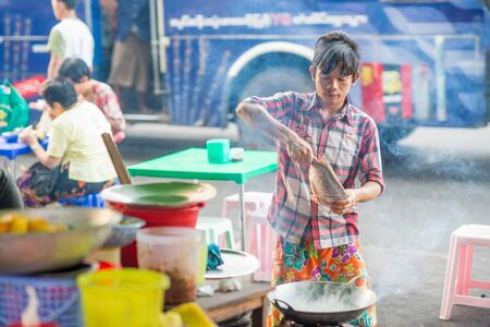 ethnically diverse: Yangon, Myanmar - February 5, 2014: Young Burmese man preparing street food at the street market on Maha Bandoola Road in Chinatown. Myanmar is ethnically diverse with 51 million inhabitants belonging to 135 ethnic groups.