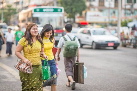 Yangon, Myanmar - February 5, 2014: Burmese women crossing a street along Maha Bandoola Road in Chinatown. Myanmar is ethnically diverse with 51 million inhabitants belonging to 135 ethnic groups. Editorial
