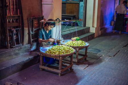 ethnically diverse: Yangon, Myanmar - February 9, 2014: Burmese fruit seller at a night market in Chinatown. Myanmar is ethnically diverse with 51 million inhabitants belonging to 135 ethnic groups. Editorial