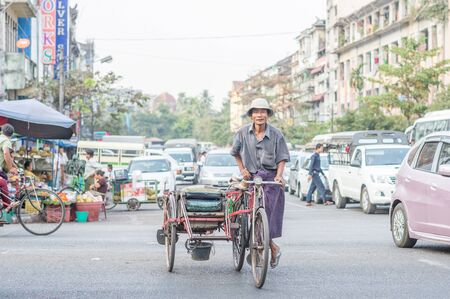 ethnically diverse: Yangon, Myanmar - February 10, 2014: Burmese rickshaw driver on Maha Bandoola Road in Chinatown. Myanmar is ethnically diverse with 51 million inhabitants belonging to 135 ethnic groups. Editorial