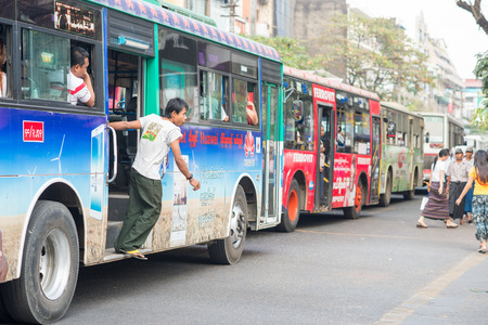 ethnically diverse: Yangon, Myanmar - February 10, 2014: Busy bus traffic on Maha Bandoola Road in Chinatown. Myanmar is ethnically diverse with 51 million inhabitants belonging to 135 ethnic groups.