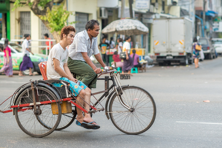 51: Yangon, Myanmar - February 10, 2014: Burmese rickshaw driver with a passenger on Maha Bandoola Road in Chinatown. Myanmar is ethnically diverse with 51 million inhabitants belonging to 135 ethnic groups.