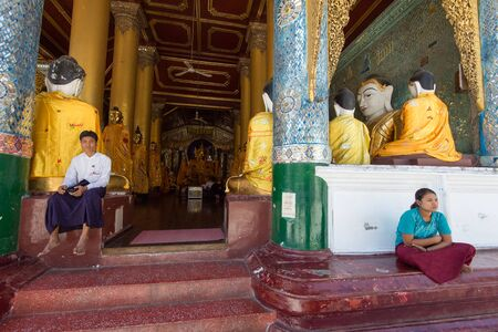 begun: Yangon, Myanmar  February 5, 2014: Burmese people enjoy the tranquility in a temple at Shwedagon Pagoda in Yangon. The temple was begun in the 5th century BC and the famous golden stupa was completed 1500 years ago.