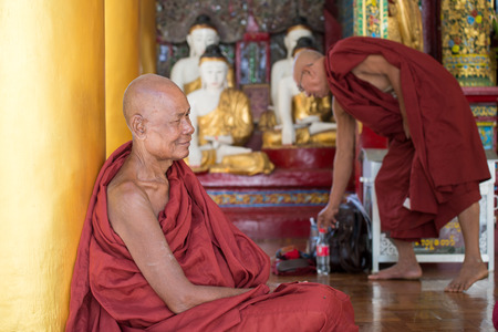 begun: Yangon, Myanmar  February 5, 2014: Burmese monks resting in a temple at Shwedagon Pagoda in Yangon. The temple was begun in the 5th century BC and the famous golden stupa was completed 1500 years ago. Editorial