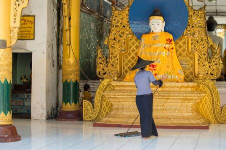 begun: Yangon, Myanmar  February 5, 2014: Burmese woman cleaning the floor in a temple at Shwedagon Pagoda in Yangon. The temple was begun in the 5th century BC and the famous golden stupa was completed 1500 years ago.