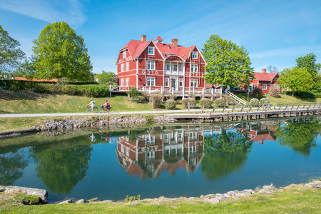 Borensberg, Sweden - May 12, 2016: Gota Canal and Gota Hotel during spring in Borensberg. The canal contributes to a 390 km long waterway with 58 locks connecting the Swedish west coast with the east coast.