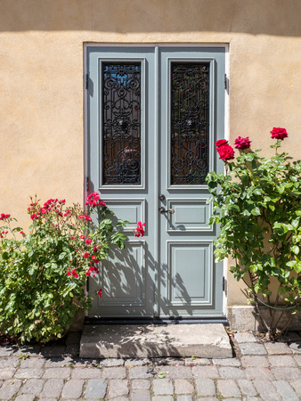 flanked: Old door flanked by roses in the historic Hanse town Visby on Swedish Baltic sea island Gotland.