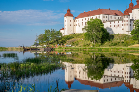 voted: Lidkoping, Sweden - July 23, 2016: Summer evening by Lake Vanern and Lacko Castle. Lacko castle dating back to the 13th century has been voted as the most beautiful castle in Sweden.