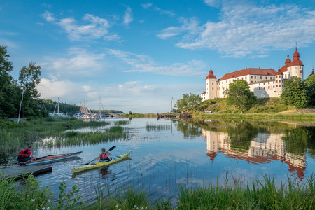 voted: Lidkoping, Sweden - July 23, 2016: Tourists kayaking on a summer evening by Lake Vanern and Lacko Castle. Lacko castle dating back to the 13th century has been voted as the most beautiful castle in Sweden.