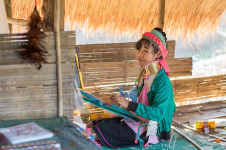 neck girl: Chiang Rai, Thailand - February 4, 2016: Karen long neck girl weaving  in a village between Chiang Rai and Chiang Mai. Karen is one of several ethnic hill tribes in northern Thailand