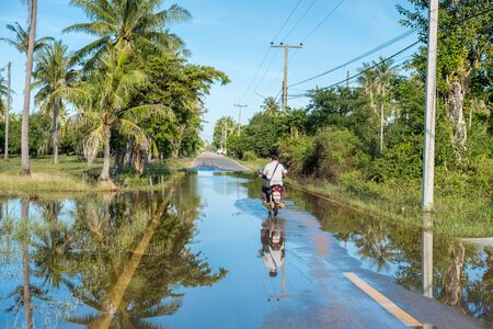 khan: Hua Hin, Thailand - January 13, 2017:Motorbiker driving in the countryside south of Hua Hin after heavy rain. The wet season in Thailand was delayed in 2016 with heavy rains continuing into January 2017.