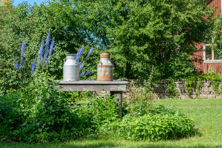 Traditional milk churn stand along a countryroad on Swedish Baltic sea island Oland for transport of milk cans to the dairy Stock Photo