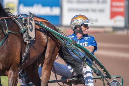 Mantorp, Sweden - June 4, 2016: Harness race driver Björn Goop preparing a horse at Mantorp race track. Björn Goop won Prix d'Amerique 2018 considered to be the biggest race in the world.