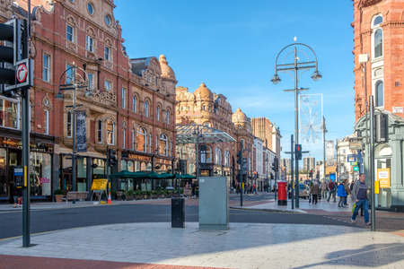 Leeds, England - October 24, 2018: Leeds Victorian and Edwardian Shopping Arcades (left) in the city center of Leeds, UK. The historic arcades in the Victoria quarter are a center for luxury shopping.