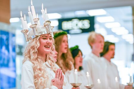 Norrkoping, Sweden - December 13, 2019: Traditional celebration of Saint Lucy in Sweden. Norrkoping's Lucia 2019 Izabella Swartz singing Christmas carols in shopping mall Linden.
