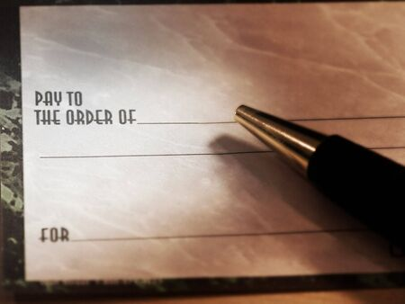 blank check: A combination greyscale and colored blank check with a pen