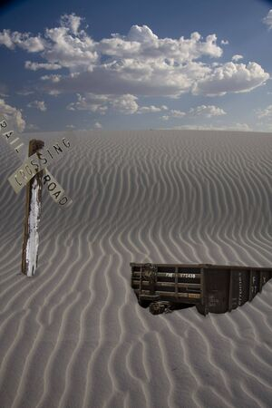 Train car and sign burried in sand
