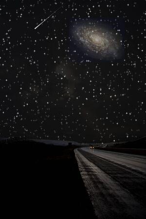 Single car travels on dark road under stars photo