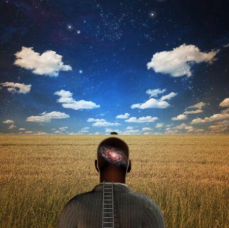 초현실적 인 들판에 머리에 은하계를 가진 남자 스톡 콘텐츠