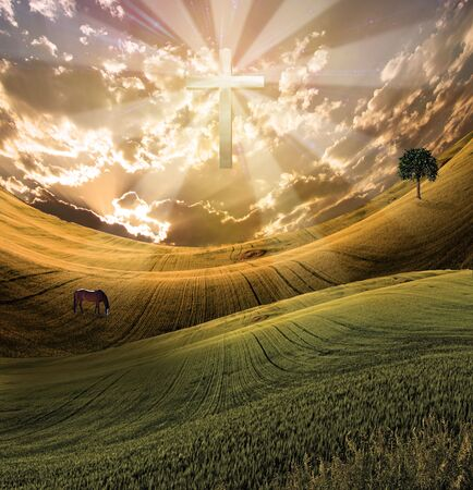 Cross radiates light in sky over beautiful landscape Stock Photo