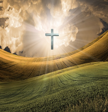 heaven: Cross radiates light in sky over beautiful landscape Stock Photo