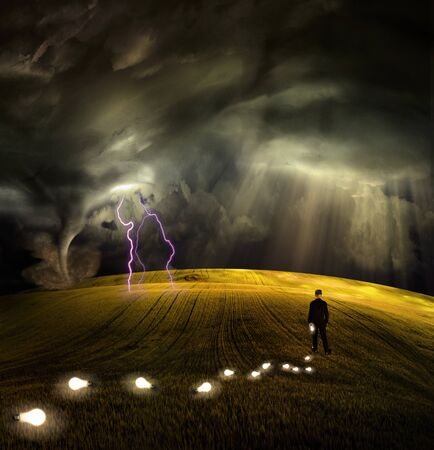 Man leaves trail of ideas in stormy field Stock Photo - 9109266