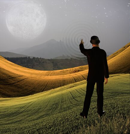 Man touches sky in landscape creting ripples in the scene photo