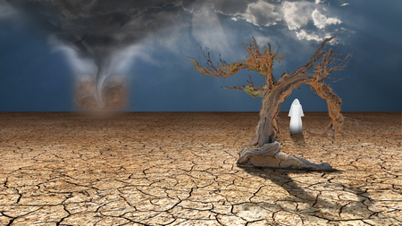 Holy Wanderer on dried desert mud faces desert dust devil Stock Photo