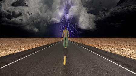 Man on road confronts storm photo