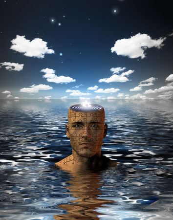 introspection: Man immersed in water with glowing puzzle piece in opened mind