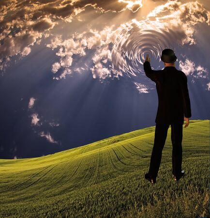 sci: Man touches sky in landscape creting ripples in the scene Stock Photo