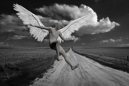 Naked man with angel wings coming down to the Earth. Banque d'images
