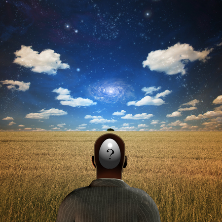 Man with questions in his head stands on the field of wheat