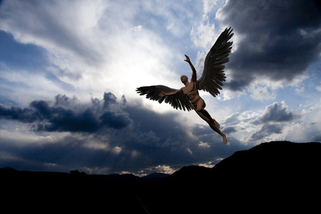 Naked man with white wings in cloudy sky symbolizes angel. Stock Photo