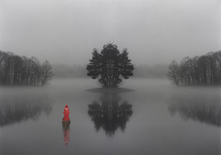 Figure in red cloak floats in boat in mystic forest lake 스톡 콘텐츠