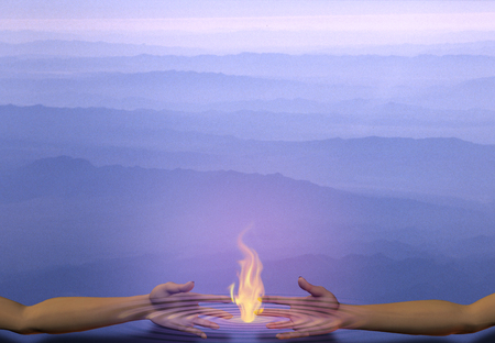 Hands touches fire. Abstract blue background