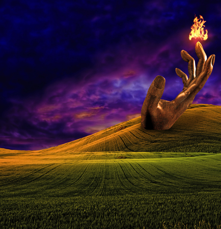 Surreal landscape with giant sculpture of hand and fire Stock Photo